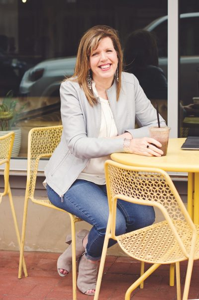 Suzie sitting at a yellow table with coffee