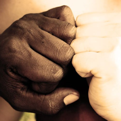 A black and a white hand touching