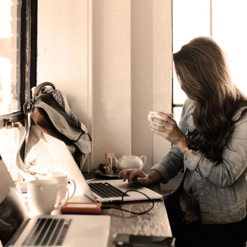 woman sitting and typing while drinking coffee